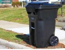 A black garbage can sitting on a curb.