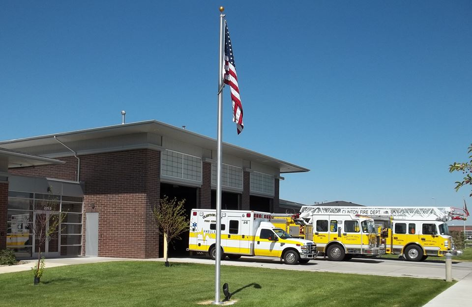 The Clinton Fire Department building with a yellow ambulance, and 2 yellow fire trucks.